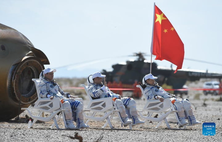 Astronauts Nie Haisheng (C), Liu Boming (R) and Tang Hongbo are out of the return capsule of the Shenzhou-12 spaceship at the Dongfeng landing site.
