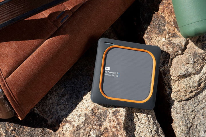 The Western Digital My Passport Wireless SSD next to rocks and a travel pack.