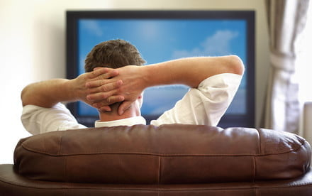 sling tv expands spanish language programming 25151395 man sitting on a sofa watching with hands folded behind his head jpg