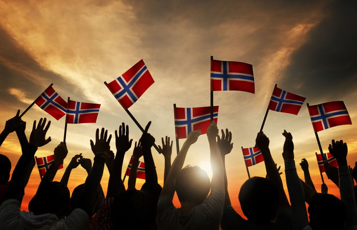 norway ev incentives extended 31310464  group of people waving norwegian flags in back lit