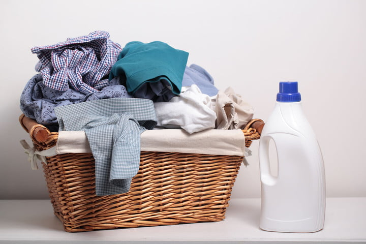 how much laundry detergent should you use 38735149  dirty clothes in the basket and a bottle of