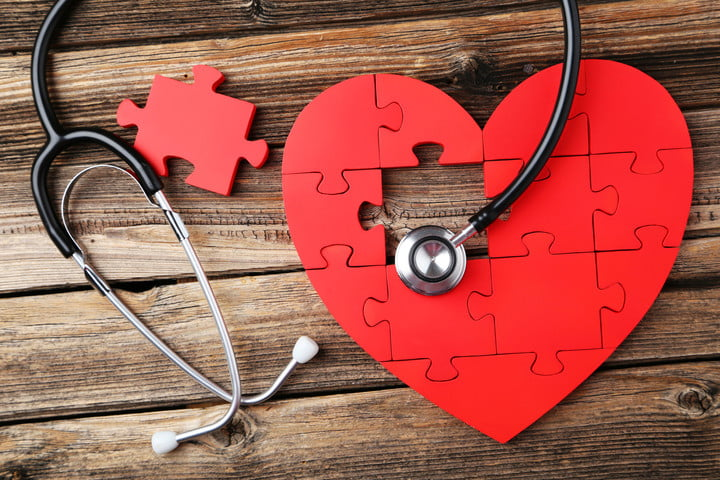 40576178 - red puzzle heart with stethoscope on brown wooden background