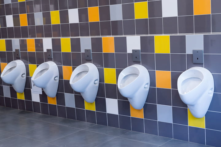 splashproof urinal research 40640071  white porcelain urinals against a yellow and orange tiled wall
