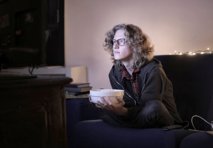 A photo of someone watching a movie on their couch.