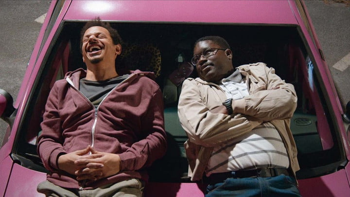 Eric André and Lil Rel Howery lying on top of a car in a scene from Bad Trip.
