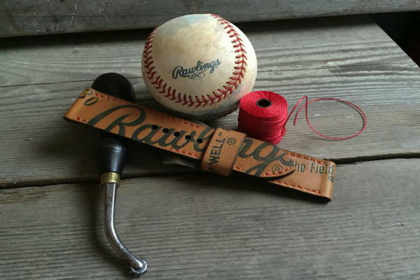 The Strap Smith Baseball Glove Strap next to a baseball and red thread.