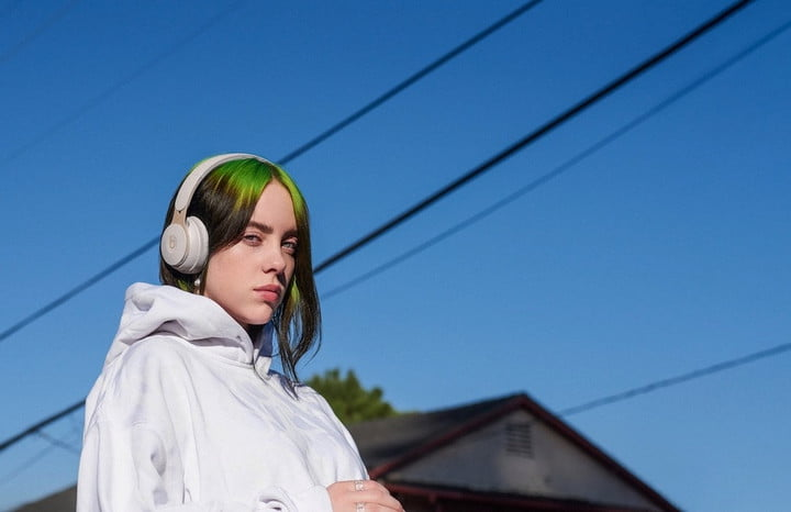 Billie Eilish outside in a pair of Beats Solo Pro wireless headphones.