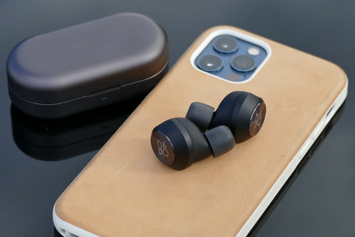 Beoplay EQ earbuds on top of an iPhone 12 Pro.