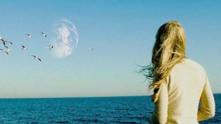 A woman looking out over the ocean and seeing a second Earth in the sky.