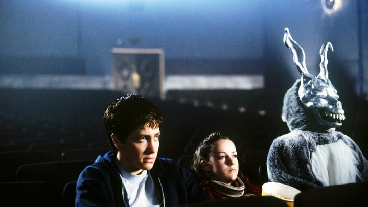 Jake Gyllenhaal as Donnie Darko, in a theater with the creepy rabbit that haunts him.