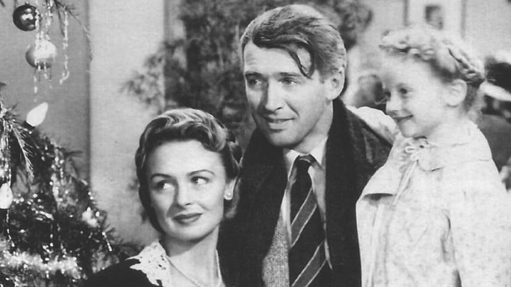 Jimmy Stewart as George Bailey with his wife and daughter.
