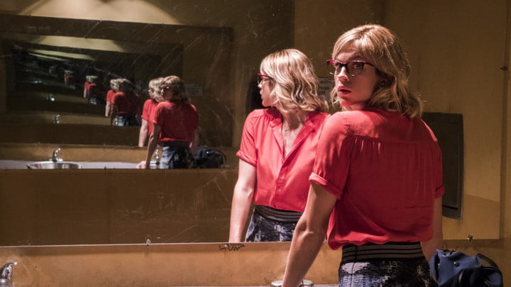 A woman standing in front of a mirror that is showing endless reflections of her.