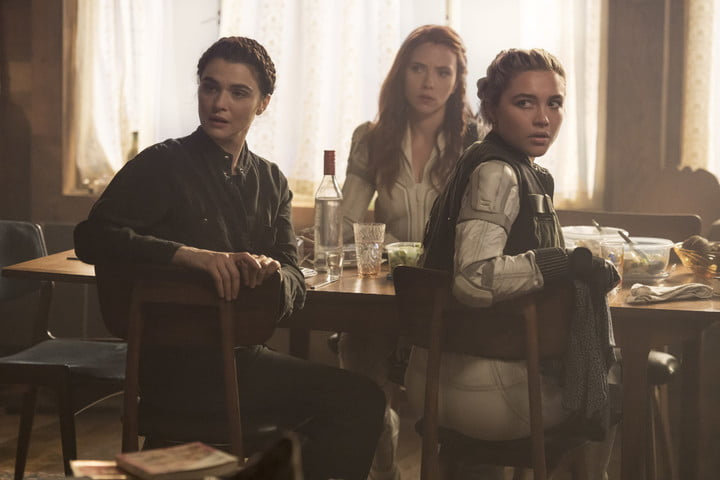 Rachel Weisz, Scarlett Johansson, and Florence Pugh sit at a table in a scene from the Black Widow movie.