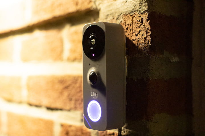 Blue by ADT doorbell button lit up at night.