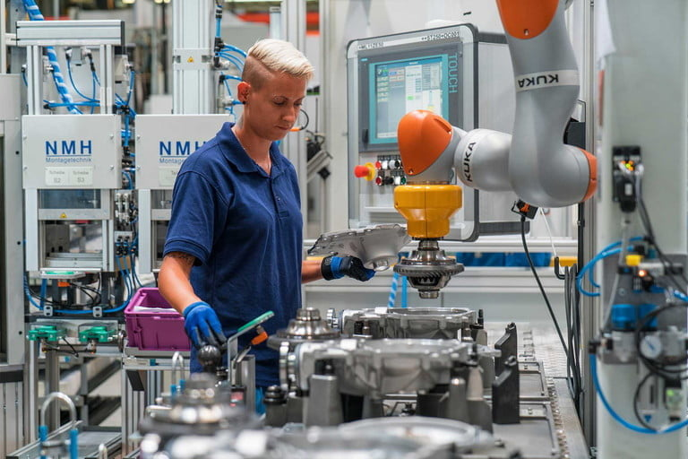 BMW factory worker using robotic arm
