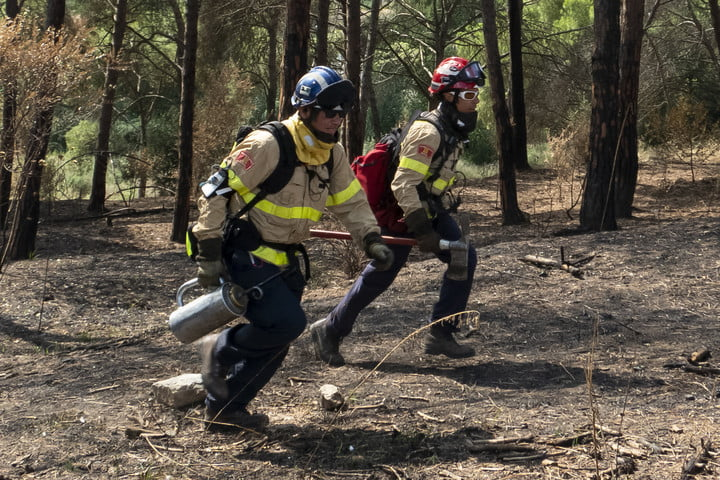 Firefighters running through the woods wearing Prometeo device