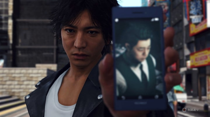 The main character of Judgment shows a picture on his phone to someone.