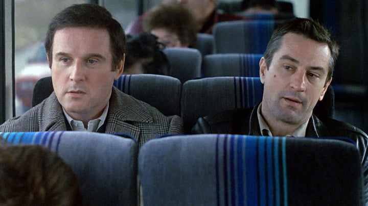Charles Grodin and Robert De Niro seated on a train in the film Midnight Run.