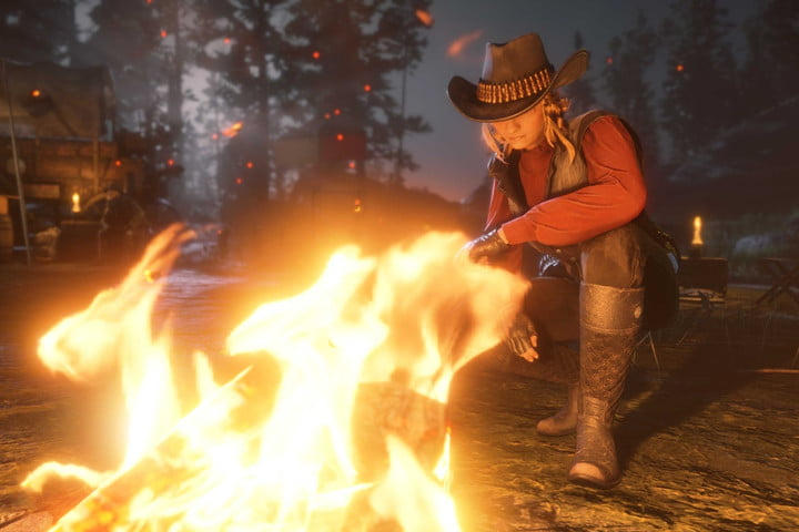 A female player crafts by a fire in Red Dead Online.