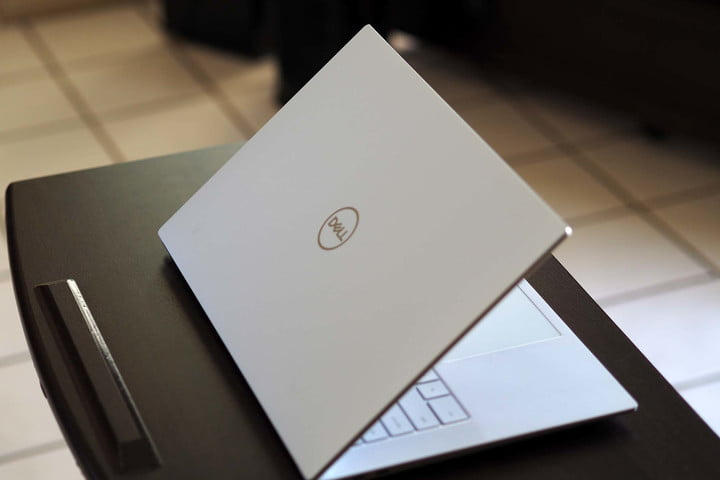 Dell XPS 15 OLED laptop sitting on a small table. View of the backside.