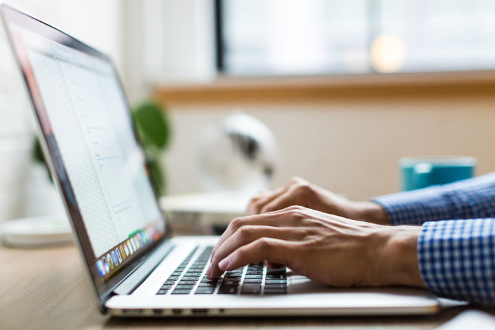 A man's hands typing on a laptop.