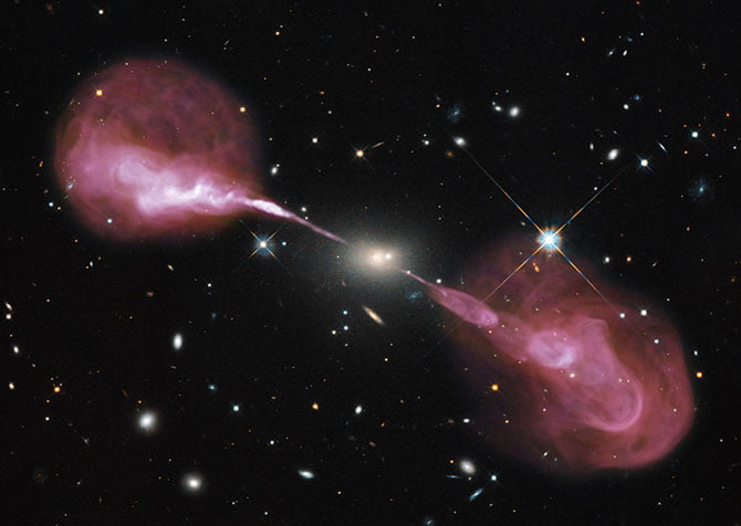 The radio galaxy Hercules A has an active supermassive black hole at its centre. Here it is pictured emitting high energy particles in jets expanding out into radio lobes.