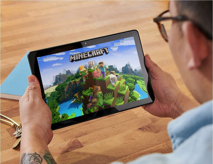 Amazon Fire 10 HD Plus tablet with user playing Minecraft.