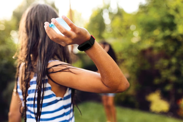 Child wearing the Fitbit Ace 3 while throwing a water balloon.