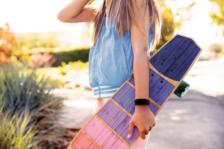A girl holding onto skateboard while wearing Fitbit Ace 3.
