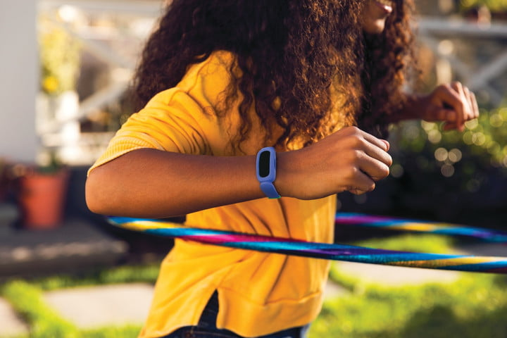 Fitbit Ace 3 worn around the wrist of a child using a hula hoop.