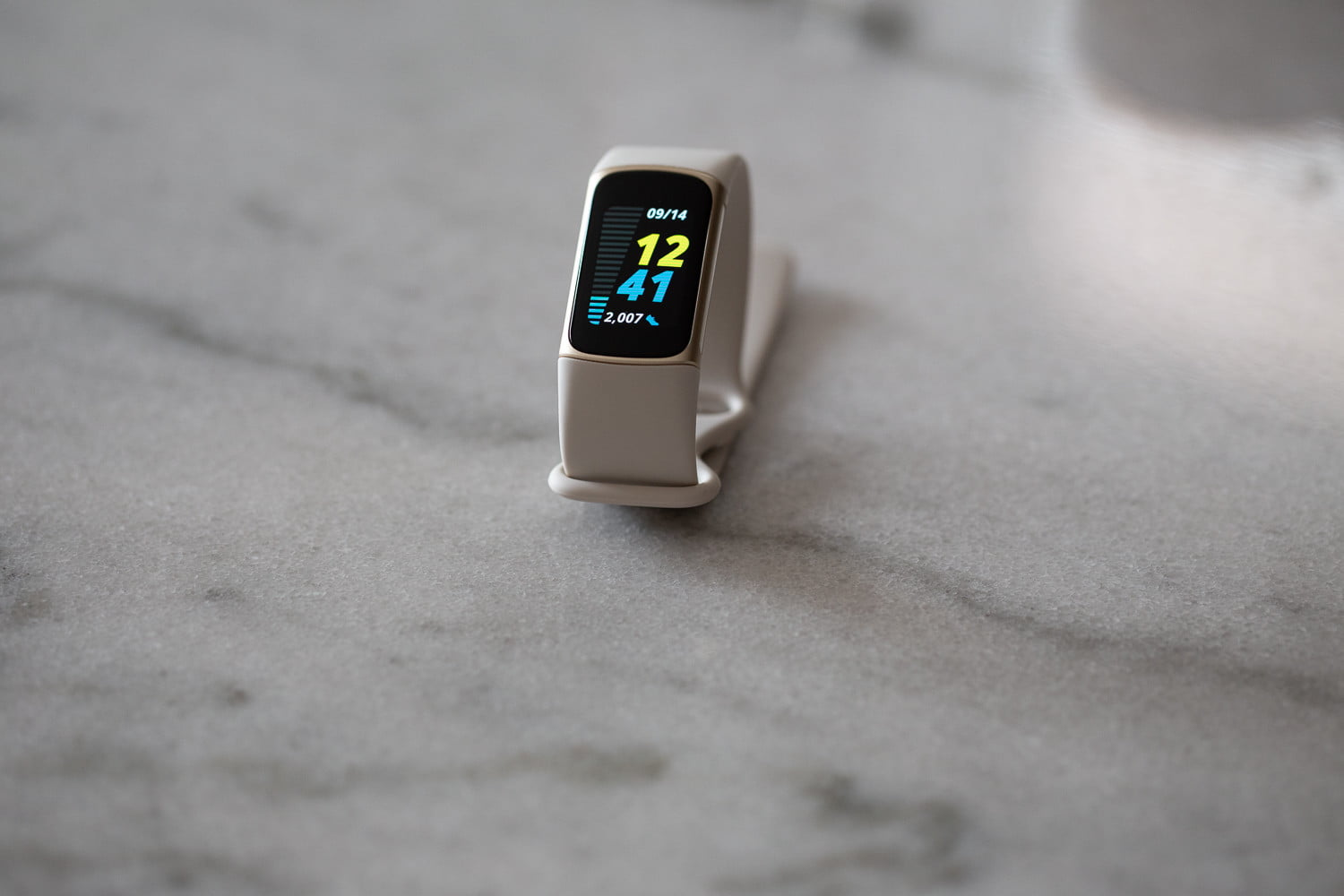 A freestanding Fitbit Charge 5 displaying the home screen.