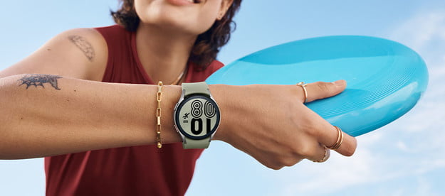 Person holding a frisbee while holding the Samsung Galaxy watch4 classic fitness.