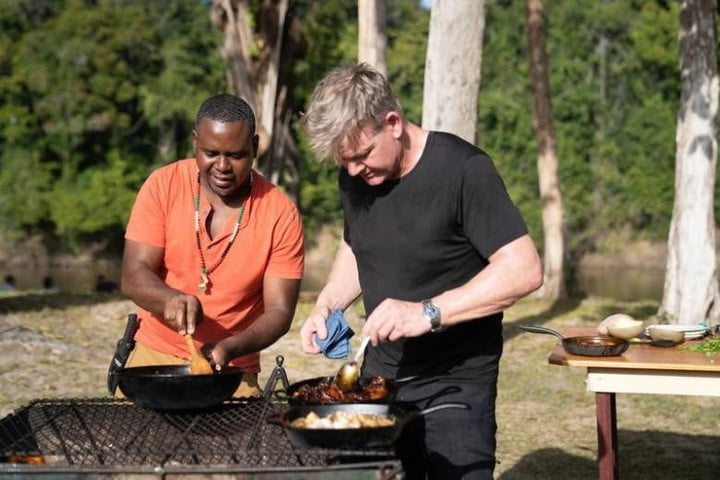 Gordon Ramsay assists in preparing a meal in a scene from Gordon Ramsay: Uncharted.