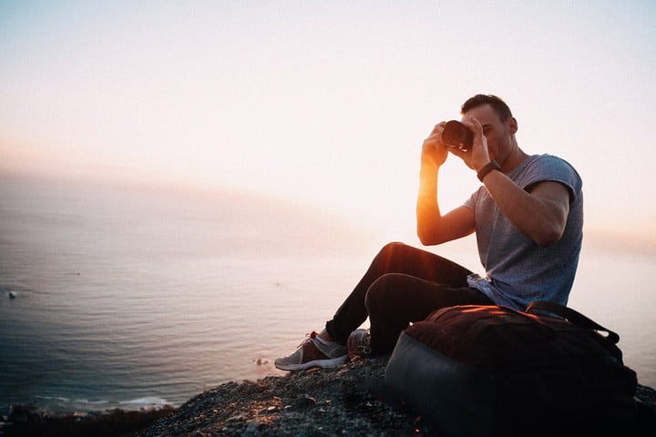 videoblocks is now storyblocks graphicstock young male adult taking photos with camera while sitting on edge of mountain beau
