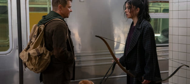 Jeremy Renner and Hailee Steinfeld stand in front of a subway car in a scene from Hawkeye.