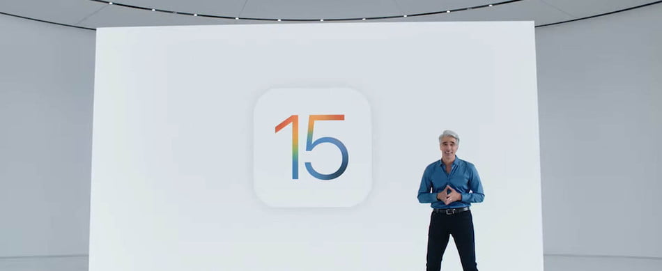 Apple's Craig Federighi standing in front of the iOS 15 logo.
