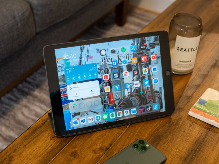 Apple iPad 8th Gen on a table showing the screen and apps.