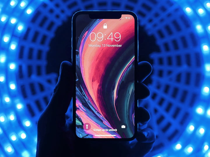 An iphone 12 with neon lighting backdrop.
