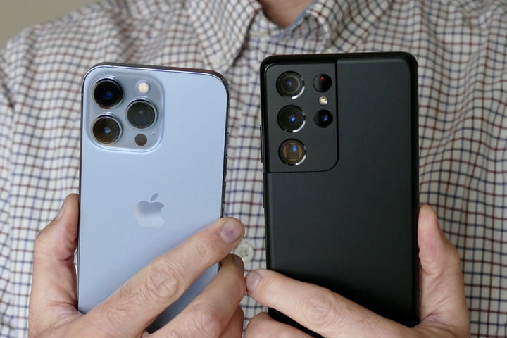 The iPhone 13 Pro and Galaxy S21 Ultra held in hand.