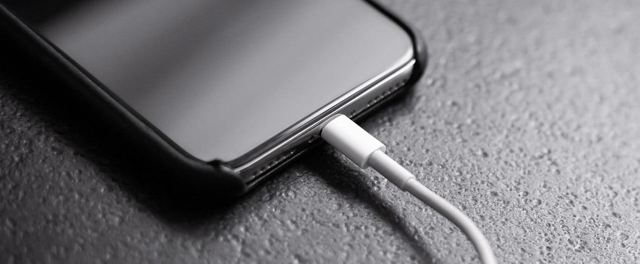 Black iPhone 11 plugged into charger.