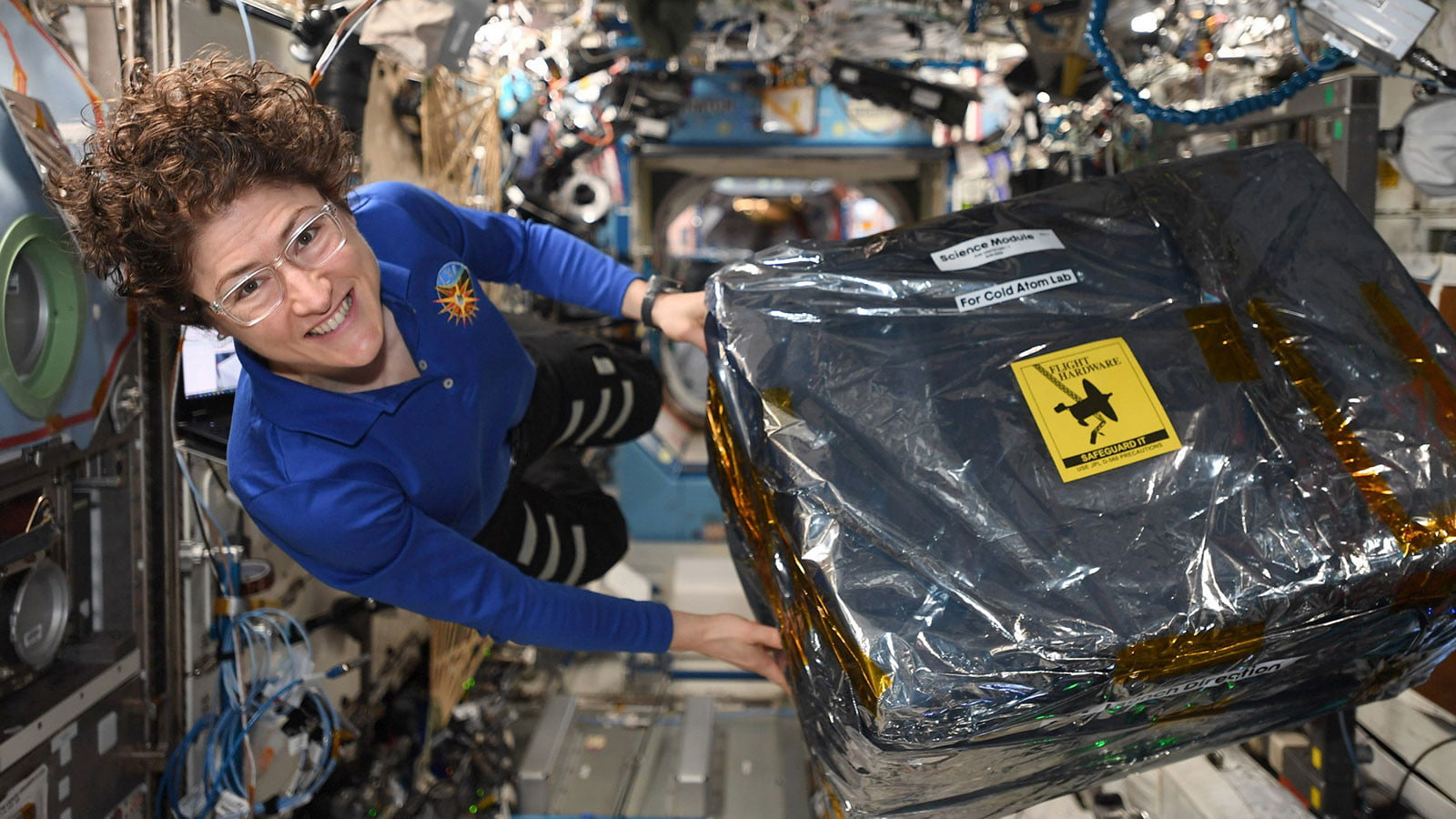 ISS astronaut Christina Koch unloads new hardware for the Cold Atom Lab.