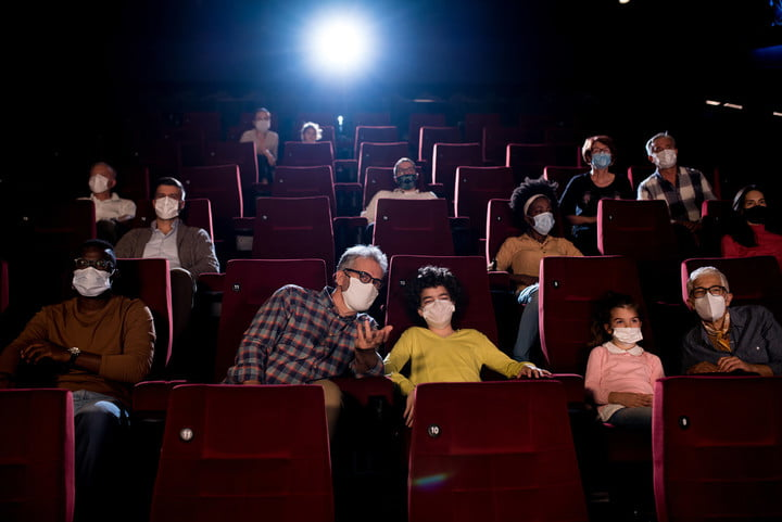 Kids and their grandparents wearing protective face masks while watching movies at the cinema.