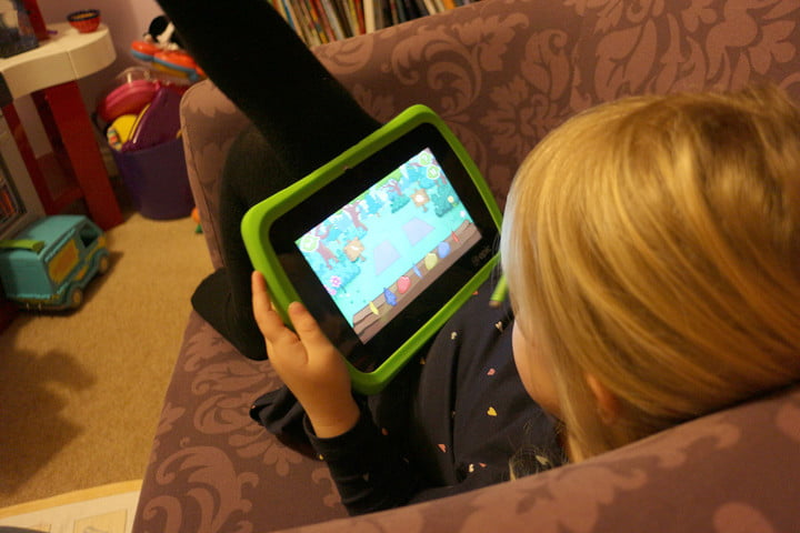 LeapFrog Epic in a child's hands showing the screen and bright green bumper.