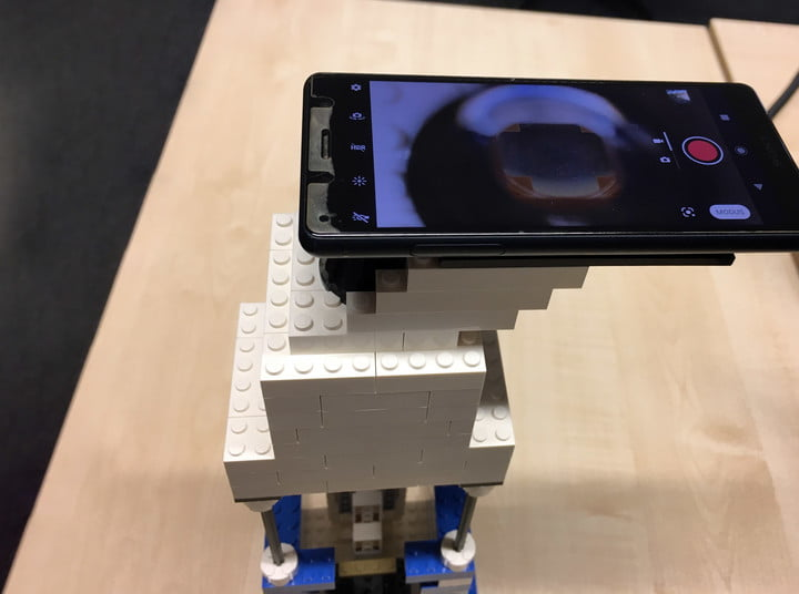 A mobile phone mounted on the top of a Lego microscope, serving as a lens.