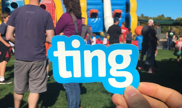 Ting logo sign being held in the foreground with a crowd and a bouncy castle in the background.