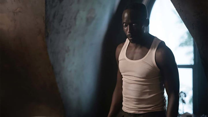 Michael K. Williams with his head down in a tank top in a scene from Lovecraft Country.