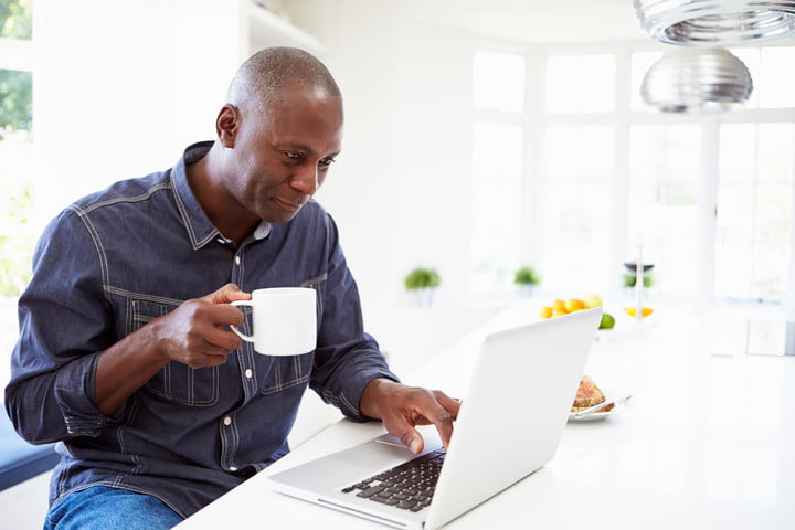 how to download torrents man downloading on computer with coffee