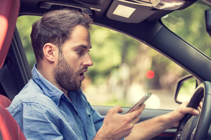 france texting while driving man sitting in car with mobile phone hand