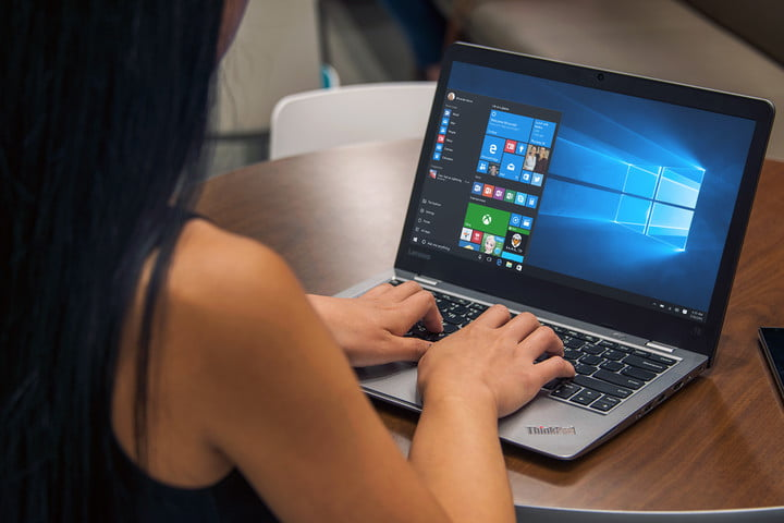 A woman sits by a desk and types on a laptop that runs Windows 10.