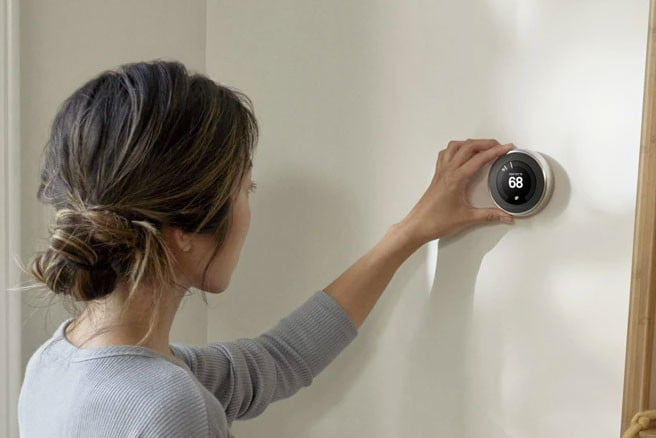 Photo of a woman adjusting a Nest Thermostat.